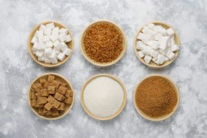 Various types of sugar, brown sugar and white on concrete backgr