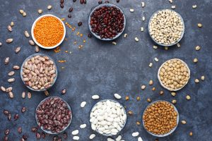 Legumes and beans assortment in different bowls on light stone b
